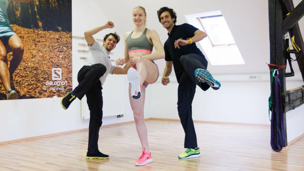 Mlada športnica v družbi spremljevalne ekipe kineziologov v telovadnici.