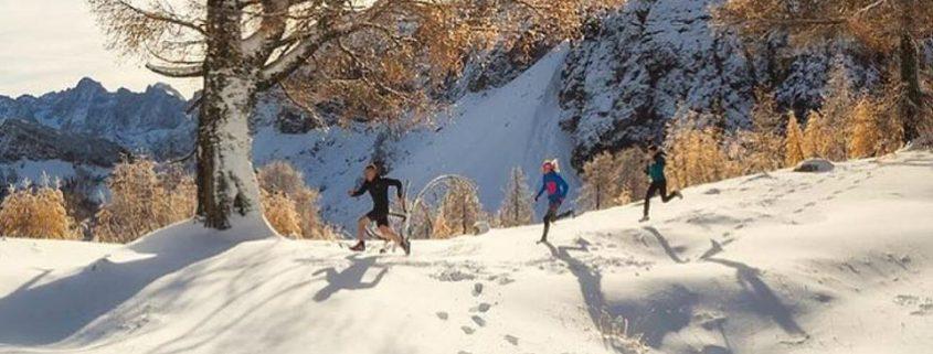 Trail tekači tečejo v zimski idili slovenskih gora.