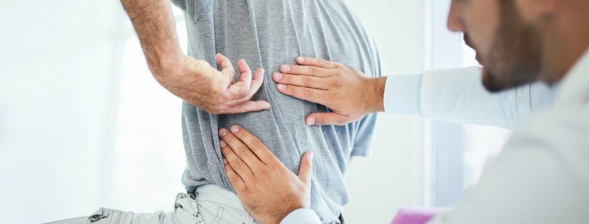 Terapevt pregleduje pacienta z bolečinami v hrbtu.