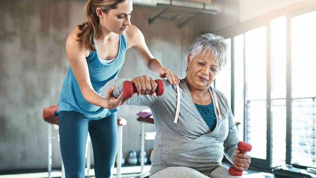 Starejša gospa telovadi s trenerko.