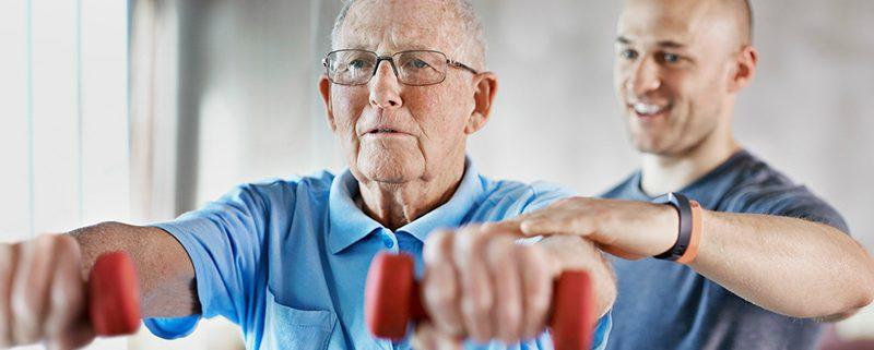 Starejši gospod telovadi z utežmi v rokah skupaj s kineziologom.