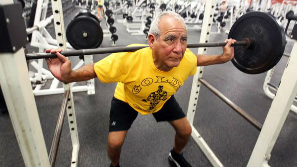 Starejši gospod v fitnesu dviguje uteži.