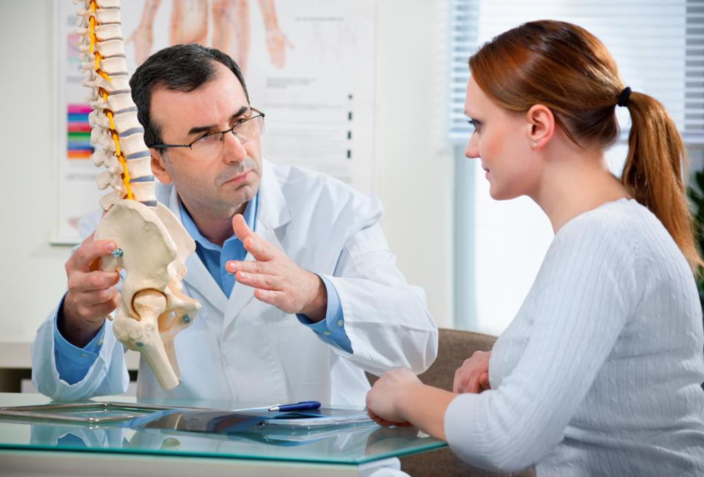 Terapevt se pogovarja s pacientko in ji razlaga o bolečini v hrbtenici.
