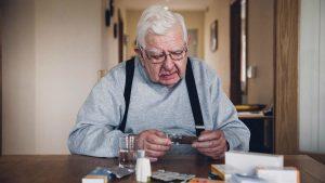 Starejši gospod sedi za mizo in šteje tablete.