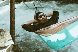 Moški spi v viseči mreži nad rečno strugo.