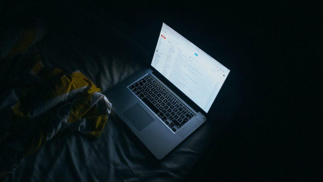 Prižgan prenosni računalnik v temi na postelji.